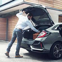 Hombre abriendo el maletero detrás de un Honda Civic 5 puertas