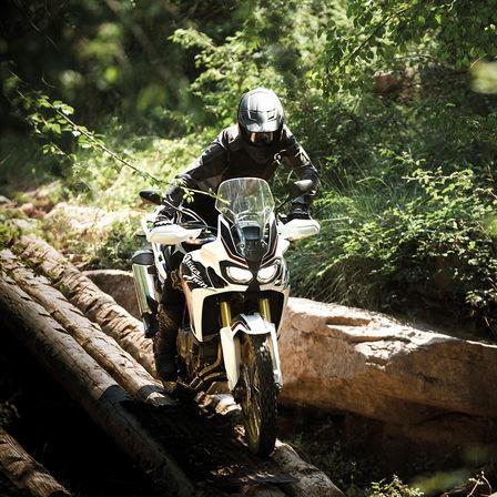 Moto atravesando un puente de troncos