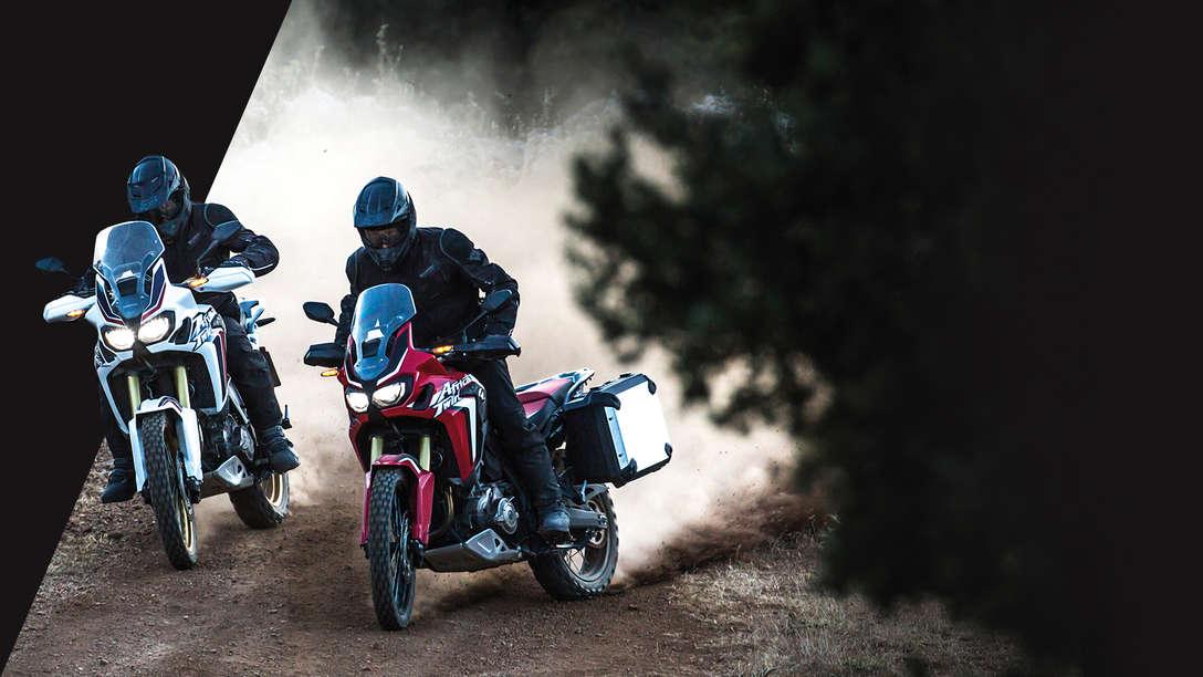 Dos motocicletas Africa Twin circulando por un camino forestal